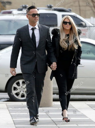 """Michael """"The Situation"""" Sorrentino, left, one of the former stars of the """"Jersey Shore"""" reality TV show walks with his fiancee Lauren Pesce while arriving at the Martin Luther King, Jr., Federal Courthouse for a hearing, in Newark, N.J. Sorrentino, who is expected to plead guilty to cheating on his taxes, and his brother, Marc, were charged in 2014 and again last year with multiple counts related to nearly $9 million in income from the show. They had pleaded not guilty, but wrote a letter to the judge this week stating they wanted to change their pleas"""