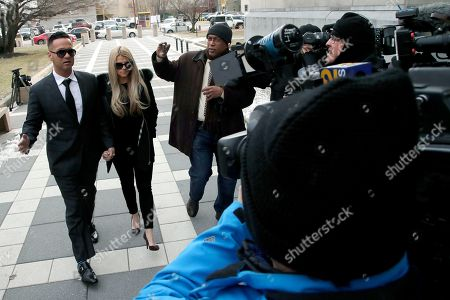 """Michael """"The Situation"""" Sorrentino, left, one of the former stars of the """"Jersey Shore"""" reality TV show walks with his fiancee Lauren Pesce as reporters swarm them while arriving at the Martin Luther King, Jr., Federal Courthouse for a hearing, in Newark, N.J. Sorrentino, who is expected to plead guilty to cheating on his taxes, and his brother, Marc, were charged in 2014 and again last year with multiple counts related to nearly $9 million in income from the show. They had pleaded not guilty, but wrote a letter to the judge this week stating they wanted to change their pleas"""