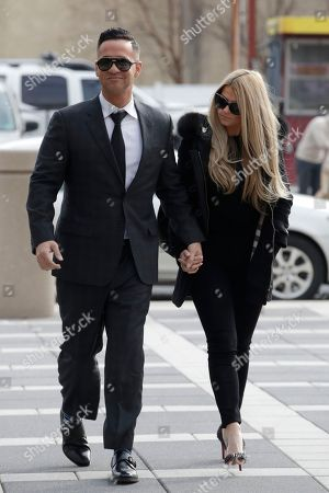 """Michael """"The Situation"""" Sorrentino, left, one of the former stars of the """"Jersey Shore"""" reality TV show, walks with his fiancee Lauren Pesce while arriving at the Martin Luther King, Jr., Federal Courthouse for a hearing, in Newark, N.J. Sorrentino, who is expected to plead guilty to cheating on his taxes, and his brother, Marc, were charged in 2014 and again last year with multiple counts related to nearly $9 million in income from the show. They had pleaded not guilty, but wrote a letter to the judge this week stating they wanted to change their pleas"""