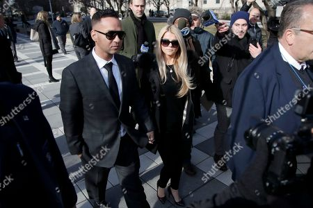 """Michael """"The Situation"""" Sorrentino, left, one of the former stars of the """"Jersey Shore"""" reality TV show, walks with his fiancee Lauren Pesce while leaving the Martin Luther King, Jr., Federal Courthouse after a hearing, in Newark, N.J. Sorrentino pleaded guilty to one count of tax evasion and admitted concealing his income in 2011 by making cash deposits in amounts that wouldn't trigger federal reporting requirements. He and his brother, Marc, were charged in 2014 and again last year with multiple counts related to nearly $9 million in income from the show"""