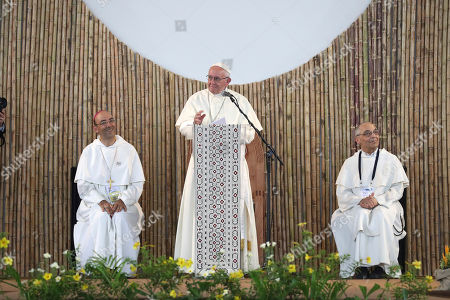 """David Martinez, Bruco Cadore, Pope Francis. Flanked by Bishop David Martinez and Father Bruco Cadore, Pope Francis speaks to a gathering of indigenous groups, in Puerto Maldonado, Peru, . Standing with thousands of indigenous Peruvians, Francis declared the Amazon the """"heart of the church"""" and called for a three-fold defense of its life, land and cultures"""