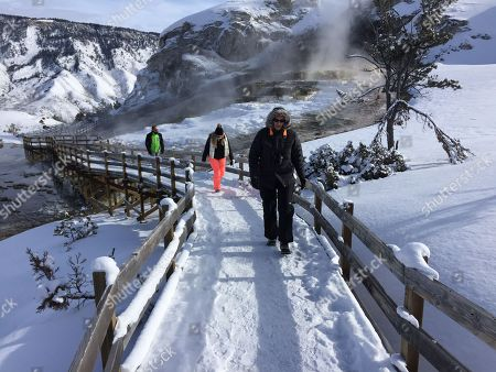 James Kristy and Ginger Lee of Palm Beach County, Fla., walk the boardwalk at Yellowstone National Park's Mammoth Hot Springs on Visitors can still ride snowmobiles and snow coaches into Yellowstone National Park to gaze at the geysers and buffalo herds, despite the federal government shutdown