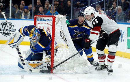 St. Louis Blues goaltender Carter Hutton, left, stops an attempt by Arizona Coyotes' Jordan Martinook, right, as Blues' Vince Dunn watches during the first period of an NHL hockey game, in St. Louis