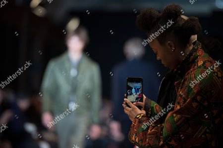 A visitor photographs models presenting creations from the Fall/ Winter 2018/2019 Ready to Wear collection by French designer Pierre Maheo for Officine Generale fashion house during the Paris Fashion Week, in Paris, France, 21 January 2018. The presentation of the Men's collections runs from16 to 21 January 2018.