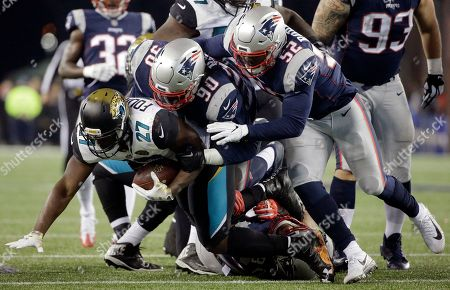 Leonard Fournette, Malcom Brown, Elandon Roberts. Jacksonville Jaguars running back Leonard Fournette (27) is tacked by New England Patriots defensive tackle Malcom Brown (90) and linebacker Elandon Roberts (52) during the second half of the AFC championship NFL football game, in Foxborough, Mass