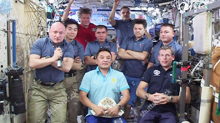 In this image made from video provided by NASA, the nine-member International Space Station crew holds a news conference for journalists around the world. From left are Scott Kelly, Kimiya Yui, Gennady Padalka, Sergey Volkov, Aidyn Aimbetov, Mikhail Kornienko, Oleg Kononenko, Andreas Mogensen and Kjell Lindgren
