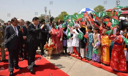 Xi Jinping, Mamnoon Hussain. In this photo provided by Pakistan's Press Information Department, Chinese President Xi Jinping waves to children with Pakistan's Present Mamnoon Hussain, left, upon his arrival at Nur Khan airbase in Islamabad, Pakistan, . Xi arrived for a two-day visit during which the two sides will launch an ambitious $45 billion economic corridor linking Pakistan's port city of Gwadar with western China