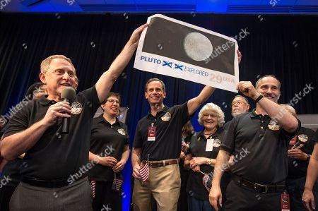 In this photo provided by NASA, New Horizons Principal Investigator Alan Stern of Southwest Research Institute (SwRI), Boulder, Colo., left, Johns Hopkins University Applied Physics Laboratory (APL) Director Ralph Semmel, center, and New Horizons Co-Investigator Will Grundy of the Lowell Observatory hold a print of a U.S. stamp with their suggested update since the New Horizons spacecraft made its closest approach to Pluto, at the Johns Hopkins University Applied Physics Laboratory (APL) in Laurel, Md. on . At center right under the stamp is Annette Tombaugh, daughter of Pluto's discoverer, Clyde Tombaugh