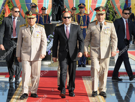 In this picture provided by the office of the Egyptian Presidency, Egyptian President Abdel-Fattah el-Sissi, center, visits the tomb of the late Egyptian President Anwar Sadat, who was assassinated in 1981, in Cairo, Egypt