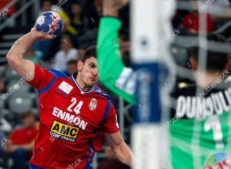 Serbia's Milan Jovanovic, left, attempts to shoot during the Eurohandball European Championships handball match between Serbia and France, in Zagreb, Croatia