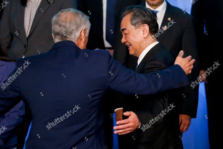 Chile's Foreign Minister Heraldo Munoz, left, embraces China's Foreign Minister Wang Yi after posing for a group picture on the sidelines of the second ministerial that is part of a forum between China and the Community of Latin American and Caribbean States (CELAC) in Santiago, Chile