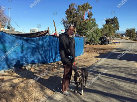 Heather Smith, She-Ra. Heather Smith, a 42-year-old homeless woman, stands with her pit bull, She-Ra, outside her tent on the riverbed trail in Anaheim, Calif., . Smith doesn't know where she'll go now that Orange County authorities are moving to clear the riverbed encampment where she lives