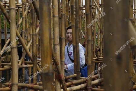 Stock Image of A man walks through the bamboo maze installation titled 'the infinite dimensions of smallness' by Thai artist Rirkrit Tiravanija on display on the roof garden at the National Gallery in Singapore, 23 January 2018. The installation consists of 2,500 bamboo poles arranged in a maze that spans over 285 square metres in area and four metres in height. It will be on display from 24 January to 28 October 2018 on the roof garden of the National Gallery in Singapore.