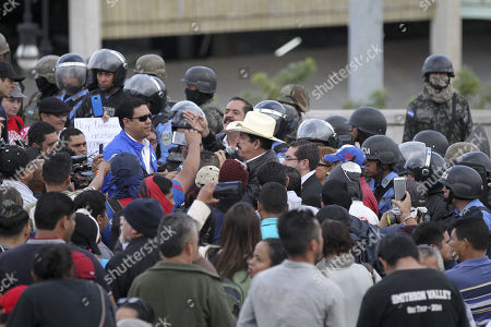 The general coordinator of the Opposition Alliance, the former president of Honduras Manuel Zelaya (C-with hat), speaks with his followers in front of a military checkpoint that prevents them from reaching the Honduran Parliament, where Mauricio Oliva (out of frame) is sworn in as president of the legislative power for the period 2018-2022 in Tegucigalpa, Honduras, 23 January 2018. The Honduran Parliament elected the board of directors headed by the ruling National Party, amid protests by the opposition against President Juan Orlando Hernandez.