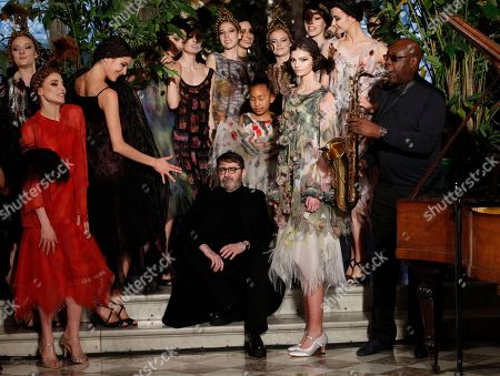 French fashion designer Franck Sorbier sits by models after the presentation of Haute Couture Spring-Summer 2018 fashion collection while saxophonist Manu Dibango performs in Paris, Wednesday, Jan.24, 2018