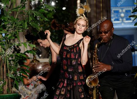 A model wears a creation for Franck Sorbier's Haute Couture Spring-Summer 2018 fashion collection presented in Paris while saxophonist Manu Dibango performs, Wednesday, Jan.24, 2018