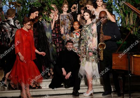 French fashion designer Franck Sorbier sits by models after the presentation of his Haute Couture Spring-Summer 2018 fashion collection while saxophonist Manu Dibango performs in Paris, Wednesday, Jan.24, 2018