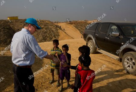 UNICEF Deputy Executive Director Justin Forsyth, left, shares biscuits with Rohingya refugee children as he leaves Balukhali refugee camp 50 kilometres (32 miles) from, Cox's Bazar, Bangladesh . Forsyth is on a two day visit to Cox's Bazar to see, first-hand, the devastating humanitarian situation of the Rohingya refugees
