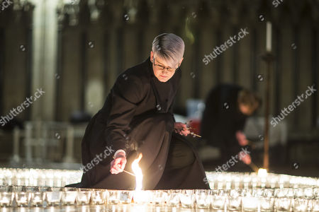 Stock Image of Verger Jessica Cook lights one of the 600 candle's being lit in the form of the Star of David in York Minster tonight in memory of more than 6 million Jews murdered by the Nazis in World War Two. The cathedral's commemoration is one of a series of events taking place across the City of York during Holocaust Memorial Week. The theme for this year's commemoration is The Power of Words.