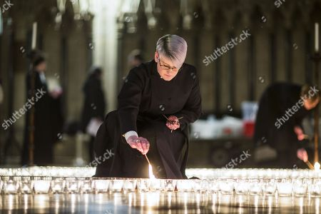 Stock Picture of Verger Jessica Cook lights one of the 600 candle's being lit in the form of the Star of David in York Minster tonight in memory of more than 6 million Jews murdered by the Nazis in World War Two. The cathedral's commemoration is one of a series of events taking place across the City of York during Holocaust Memorial Week. The theme for this year's commemoration is The Power of Words.