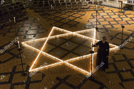 Verger Jessica Cook lights one of the 600 candle's being lit in the form of the Star of David in York Minster tonight in memory of more than 6 million Jews murdered by the Nazis in World War Two. The cathedral's commemoration is one of a series of events taking place across the City of York during Holocaust Memorial Week. The theme for this year's commemoration is The Power of Words.