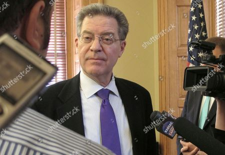 Kansas Gov. Sam Brownback answers questions from reporters after legislative leaders give the final go-ahead to a plan to build a new state prison, at the Statehouse in Topeka, Kan. The state plans to have the nation's largest private-prison operator build the new facility and lease it to the state for its first 20 years in operation