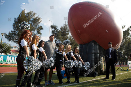 Pro Football Hall of Famer Anthony Munoz, who played 13 seasons as offensive tackle for the Cincinnati Bengals, poses for a picture with Oakland Raiders cheerleaders, during an NFL-sponsored event promoting physical activity for kids, in Mexico City, . The NFL's Play 60 campaign encourages children to be active 60 minutes a day to avoid childhood obesity. The Oakland Raiders will play the Houston Texans Monday night in Estadio Azteca in Mexico City