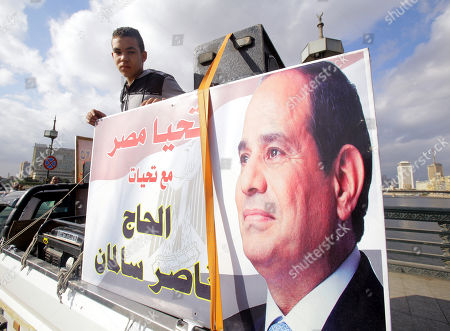 People on a truck with photo depicting Egyptian President Abdel Fattah al-Sisi drive on a bridge downtown Cairo, Egypt, 25 January 2018, on the seventh anniversary of the uprising that toppled former President Hosni Mubarak. More than 800 people were killed and thousands injured during the 18-day uprising against the Egyptian regime which led to the removal of President Hosni Mubarak on 11 February 2011.