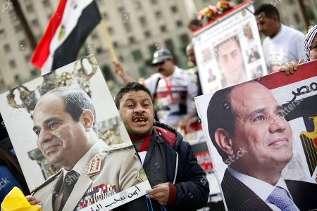 People hold photos depicting Egyptian President Abdel Fattah al-Sisi as they gather on Tahrir Square to mark the seventh anniversary of the uprising that toppled former President Hosni Mubarak, in Cairo, Egypt, 25 January 2018.  More than 800 people were killed and thousands injured during the 18-day uprising against the Egyptian regime which led to the removal of President Hosni Mubarak on 11 February 2011.