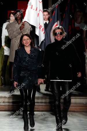 Belgian designers An Vandevorst, left, and Filip Arickx for fashion house AF Vandervorst acknowledge applause at the end of their Haute Couture Spring-Summer 2018 fashion collection presented in Paris