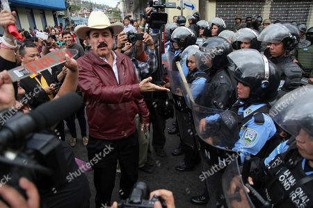 Former Honduran President Jose Manuel Zelaya, center, talks with reporters in front of a cordon of police outside the Congress during a protest against current President Juan Orlando Hernandez, in Tegucigalpa, Honduras, . Hernandez was awarded the electoral win last month despite the disputed vote tally. The opposition plans to continue protesting through his swearing-in Jan. 27