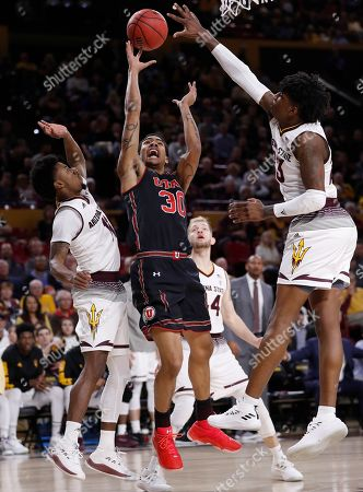 Stock Picture of Utah guard Gabe Bealer (30) shoots between Arizona State forward Romello White (23) and guard Shannon Evans II during the first half of an NCAA college basketball game,in Tempe, Ariz