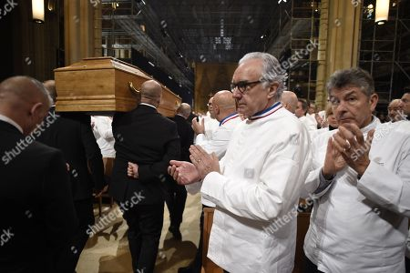 """French chefs Alain Ducasse and Regis Marcon applaud as the coffin French chef Paul Bocuse leaves the Saint-Jean Cathedral in Lyon, France, 26 January 2018. More than 1,500 chefs from around the world along with thousands of fans of French cuisine are expected in Lyon to honor their """"pope"""" Paul Bocuse, who died on 20 January 20 aged 91."""