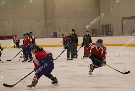 In this photo provided by South Korea Joint Government Support Corps, North Korean women's ice hockey players trains with South Korea women's hockey team head coach Sarah Murray, center, during the training at the South Korea's national training center in Jincheon, South Korea. Female hockey players from the rival Koreas were paired up with each other Thursday to form their first-ever Olympic squad during next month's Pyeongchang Winter Games, as their countries press ahead with rare reconciliation steps following a period of nuclear tensions