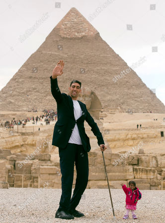 Sultan Kosen, from Turkey, 34, the tallest man on earth according to the Guinness World Records, with a height of 246.5 cm ( 8 feet 1 inch), and Jyoti Amge, from India, 24, who holds the Guinness title for world's shortest woman with 62.8 cm (2 ft 06) tall, pose for in front of the historic site of Giza Pyramids in Cairo, Egypt, . Both were invited by the Egyptian Tourism Promotion Board to visit Cairo's most famous sites, in an attempt to help boost tourism in Egypt