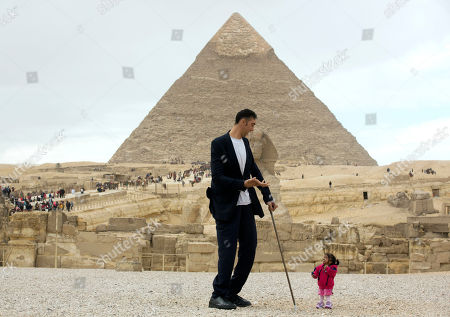 Stock Image of Sultan Kosen, from Turkey, 34, the tallest man on earth according to the Guinness World Records, with a height of 246.5 cm ( 8 feet 1 inch), talks to Jyoti Amge, from India, 24, who holds the Guinness title for world's shortest woman with 62.8 cm (2 ft 06) tall,in front of the historic site of Giza Pyramids in Cairo, Egypt, . Both were invited by the Egyptian Tourism Promotion Board to visit Cairo's most famous sites, in an attempt to help boost tourism in Egypt