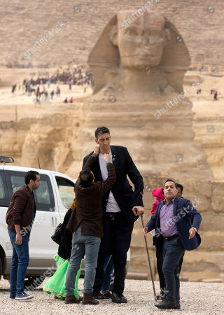 Stock Photo of Sultan Kosen, from Turkey, 34, the tallest man on earth according to the Guinness World Records, with a height of 246.5 cm ( 8 feet 1 inch), is helped by his fiend before his visit to the historic site of Giza Pyramids in Cairo, Egypt, . Sultan was invited by the Egyptian Tourism Promotion Board to visit Cairo's most famous sites, in an attempt to help boost tourism in Egypt