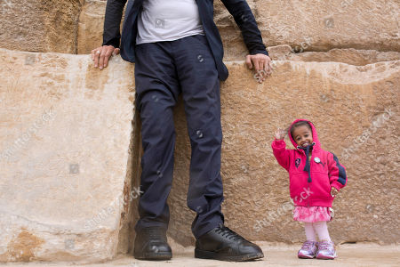 Stock Image of Sultan Kosen, from Turkey, 34, the tallest man on earth according to the Guinness World Records, with a height of 246.5 cm ( 8 feet 1 inch), stands on the Great Pyramid as Jyoti Amge, from India, 24, who holds the Guinness title for world's shortest woman with 62.8 cm (2 ft 06) tall, waves at the historic site of Giza Pyramids in Cairo, Egypt, . Both were invited by the Egyptian Tourism Promotion Board to visit Cairo's most famous sites, in an attempt to help boost tourism in Egypt