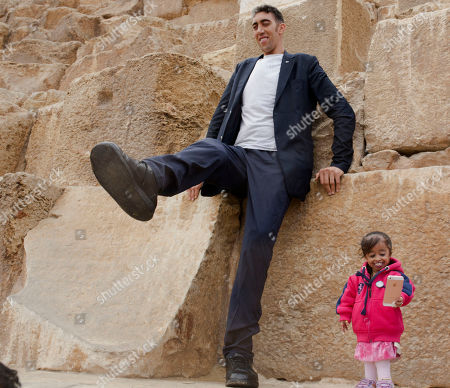 Sultan Kosen, from Turkey, 34, the tallest man on earth according to the Guinness World Records, with a height of 246.5 cm ( 8 feet 1 inch), stands on the Great Pyramid as Jyoti Amge, from India, 24, who holds the Guinness title for world's shortest woman with 62.8 cm (2 ft 06) tall, holds her mobile phone at the historic site of Giza Pyramids in Cairo, Egypt, . Both were invited by the Egyptian Tourism Promotion Board to visit Cairo's most famous sites, in an attempt to help boost tourism in Egypt
