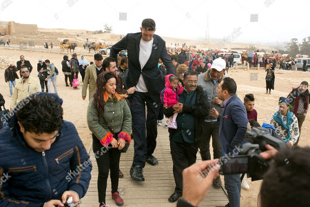 Stock Picture of Visitors watch and film Sultan Kosen, from Turkey, 34, the tallest man on earth according to the Guinness World Records, with a height of 246.5 cm ( 8 feet 1 inch), and Jyoti Amge, from India, 24, who holds the Guinness title for world's shortest woman with 62.8 cm (2 ft 06) tall, carried by her father, center right, at the historic site of Giza Pyramids in Cairo, Egypt, . Both were invited by the Egyptian Tourism Promotion Board to visit Cairo's most famous sites, in an attempt to help boost tourism in Egypt