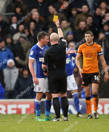 Stephen Gleeson of Ipswich Town is shown a yellow card for a dangerous challenge