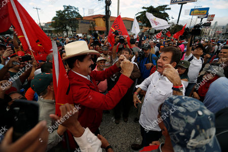 Opposition presidential candidate Salvador Nasralla, right, and former President Manuel Zelaya gather with supporters as they march against the on going swearing-in ceremony of President Juan Orlando Hernandez in Tegucigalpa, Honduras, . The opposition does not recognize Hernandez's victory following disputed poll results, and has been protesting ahead of his Jan. 27 swearing-in ceremony