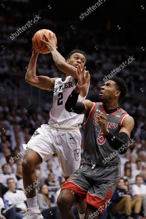 Justin Simon, Aaron Thompson. Butler guard Aaron Thompson (2) looks to pass over St. John's guard Justin Simon (5) in the first half of an NCAA college basketball game in Indianapolis