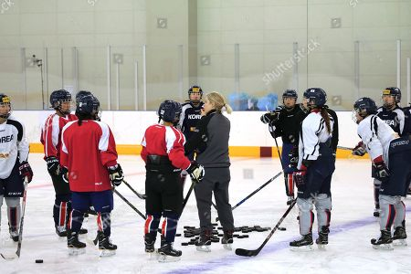 In this photo provided by Korean Sports & Olympic Committee, South Korean women's hockey team head coach Sarah Murray, center, talks to her players of North, in red, and South Koreas during a training at Jincheon national training center in Jincheon, South Korea, . North Korean officials on Saturday wrapped up a three-day visit to South Korea where they examined Olympic stadiums, hotels and concert halls that will potentially be used by North Korean athletes and other delegates headed to next month's Pyeongchang Winter Games