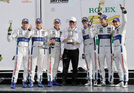 Sebastien Bourdais, Dirk Mueller, Joey Hand, Chip Ganassi, Scott Dixon, Richard Westbrook, Ryan Briscoe. Team owner Chip Ganassi, center, celebrates with his drivers, from left, Sebastien Bourdais, of France, Dirk Mueller, of Germany, Joey Hand, Scott Dixon, of New Zealand, Richard Westbrook, of Great Britain and Ryan Briscoe, of Australia, after they placed first and second in the GT LeMans class in the IMSA 24-hour auto race at Daytona International Speedway, in Daytona Beach, Fla
