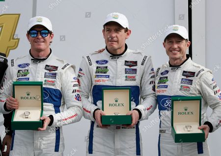 Scott Dixon, Richard Westbrook, Ryan Briscoe. Ganassi Racing team drivers, from left, Scott Dixon, of New Zealand, Richard Westbrook, of Great Britain, and Ryan Briscoe, of Australia, show off their Rolex watches they were awarded after winning the GT LeMans class in the IMSA 24-hour auto race at Daytona International Speedway, in Daytona Beach, Fla