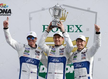 Scott Dixon, Richard Westbrook, Ryan Briscoe. Ganassi Race team drivers, from left, Scott Dixon, of New Zealand, Richard Westbrook, of Great Britain and Ryan Briscoe, of Australia hold up their trophy after winning the GT LeMans class at the IMSA 24-hour auto race at Daytona International Speedway, in Daytona Beach, Fla