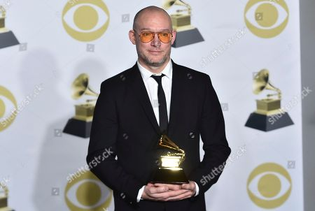 """Stock Image of Scott Devendorf, of The National, poses with the best alternative music album award for """"Sleep Well Beast"""" in the press room at the 60th annual Grammy Awards at Madison Square Garden, in New York"""