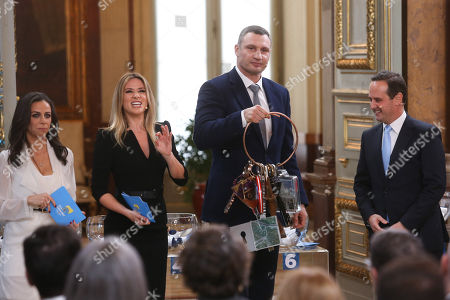 """The Mayor of Kiev Vitali Klitschko (2-R) handovers the Host City Insignia to his Lisbon counterpart Fernando Medina (R) accompanied by Portuguese television presenters Filomena Cautela (L) and Silvia Alberto (2-L) during the Semi-Final Allocation Draw Semi-Finals of the Eurovision Song Contest 2018, at the City Hall of Lisbon, Portugal, 29 of January 2018. During the Semi-Final Allocation Draw, the countries that will take part in the Semi-Finals are divided into pots, based on historic voting patterns. In this way, countries that traditionally award each other points are less likely to end up in the same Semi-Final, adding excitement to the shows. The pots are approved by the contest's Executive Supervisor on behalf of the European Broadcasting Union (EBU) and the Chairman of the Reference Group, the contest's governing body on behalf of all Participating Broadcasters. Eurovision Song Contest 2018 will take place in Lisbon in May 2018. Portugal participated in has winner of the Eurovision Song Contest 2017 contest in Kiev, Ukraine, with the song """"Amar pelos dois"""", written by Luisa Sobral and performed by her brother Salvador Sobral."""
