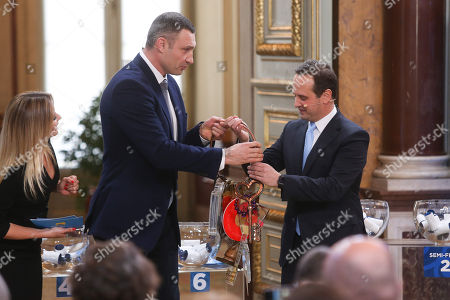 """The Mayor of Kiev Vitali Klitschko (C) handovers the Host City Insignia to his Lisbon counterpart Fernando Medina (R) during the Semi-Final Allocation Draw Semi-Finals of the Eurovision Song Contest 2018, at the City Hall of Lisbon, Portugal, 29 of January 2018. During the Semi-Final Allocation Draw, the countries that will take part in the Semi-Finals are divided into pots, based on historic voting patterns. In this way, countries that traditionally award each other points are less likely to end up in the same Semi-Final, adding excitement to the shows. The pots are approved by the contest's Executive Supervisor on behalf of the European Broadcasting Union (EBU) and the Chairman of the Reference Group, the contest's governing body on behalf of all Participating Broadcasters. Eurovision Song Contest 2018 will take place in Lisbon in May 2018. Portugal participated in has winner of the Eurovision Song Contest 2017 contest in Kiev, Ukraine, with the song """"Amar pelos dois"""", written by Luisa Sobral and performed by her brother Salvador Sobral."""